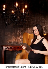 Beautiful pregnant woman in elegant black dress sitting in hotel lobby holding handheld tablet.