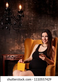 Beautiful pregnant woman in elegant black dress sitting in hotel lobby holding handheld phone.