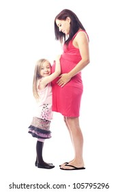 Beautiful pregnant woman expecting second child standing beside her daughter