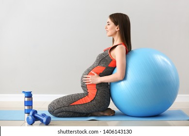 Beautiful pregnant woman with fitball training near grey wall