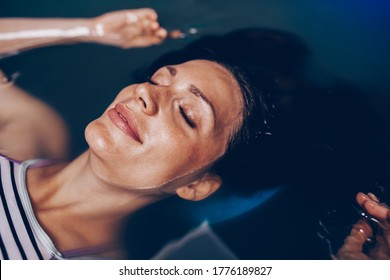 Beautiful pregnant woman floating in tank filled with dense salt water used in meditation, therapy, and alternative medicine.