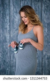 Beautiful pregnant woman in gray summer dress stands in front of wooden background and holding little baby sneakers booties newborn shoes in her hands.