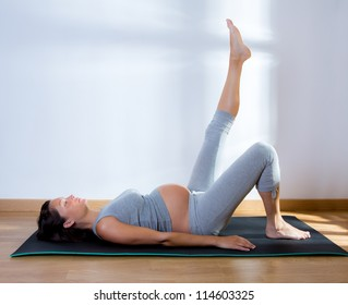 Beautiful pregnant woman at gym fitness exercise practicing aerobics on mat