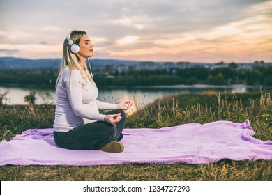 Beautiful pregnant woman with headphones enjoys meditating outdoor.Toned image.