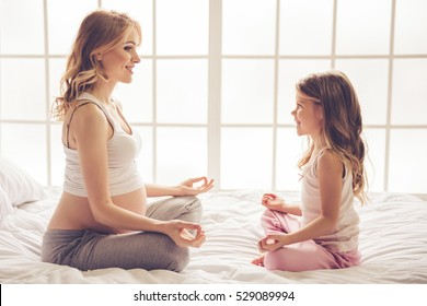 Beautiful pregnant woman and her cute little daughter are sitting in lotus position and smiling while meditating at home