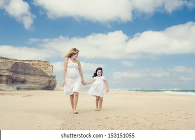 Beautiful pregnant woman and her little daughter walking on the beach