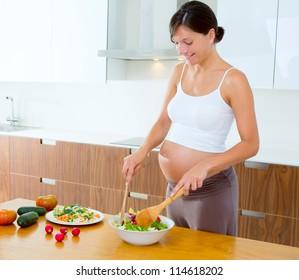Beautiful pregnant woman at home kitchen preparing salad