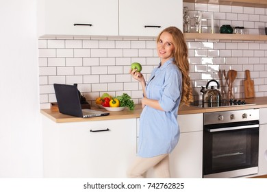 Beautiful pregnant woman with laptop in kitchen Searching recipe or food delivery Holding green apple Healthy food concept