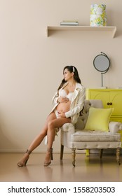 A beautiful pregnant woman with long legs in a raincoat sits on the edge of a chair and holds her hands on her stomach
