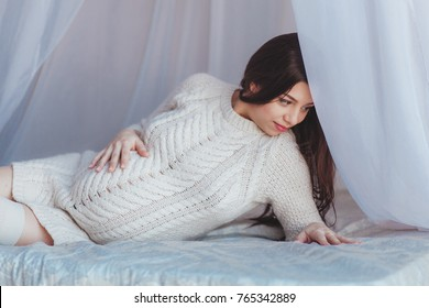 Beautiful Pregnant Woman lying in bed with canopy. Wears white knitted pullover. Maternity concept