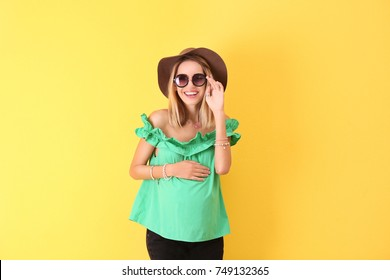 Beautiful pregnant woman on yellow background