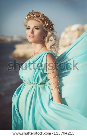 8fc13de3821 Beautiful pregnant woman outdoor in Greek goddess style with her tummy on  sunset near sea. Young happy girl showing her belly and waiting for little  baby.