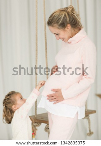 d639b9a0ee2aa Beautiful pregnant woman in a pink home suit plays with her eldest  daughter, shows her her tummy. girl touches her mother's pregnant belly.  motherhood, ...