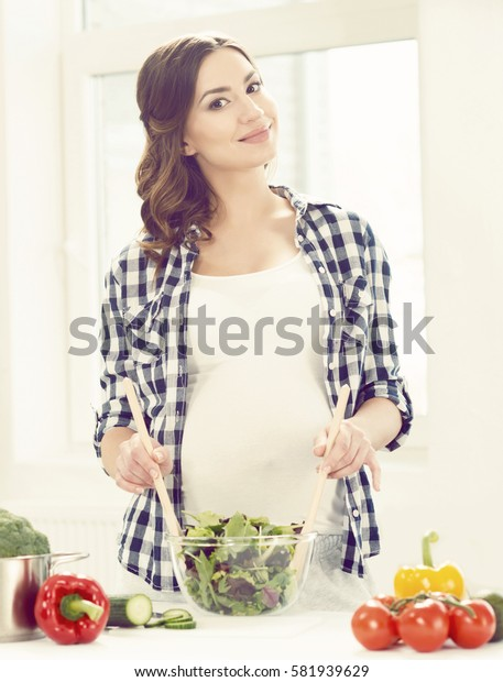 Beautiful pregnant woman preparing breakfast in kitchen. Motherhood, pregnancy, maternity concept.
