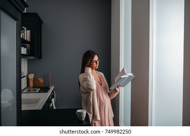 A beautiful pregnant woman is reading a pregnancy related book in her kitchen while drinking coffee.