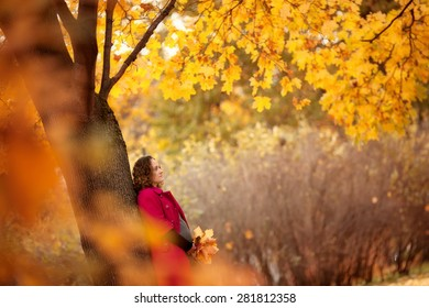 beautiful pregnant woman in red coat is standing under the yellow tree in the autumn park
