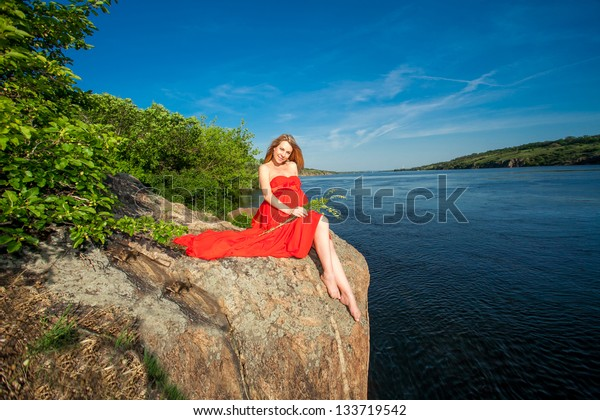 Beautiful pregnant woman in red outdoor