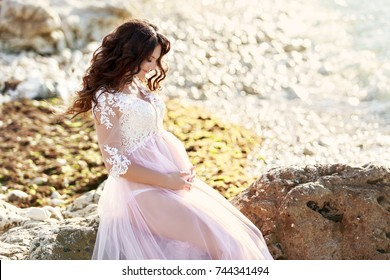 Beautiful Pregnant Woman in romantic flying dress at  sea shore near ancient ruins of Greece city. Gorgeous pregnant girl in Greek Goddes style outdoors. Brunette long hair lady - happy pregnancy.