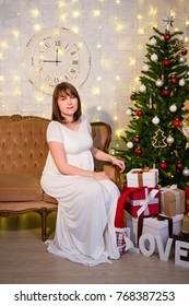beautiful pregnant woman in room with decorated christmas tree, vintage sofa, lights and gifts