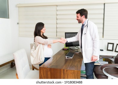 Beautiful pregnant woman shaking hands with her male gynecologist at his desk. Happy doctor greeting his female patient at the office