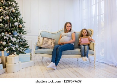 Beautiful pregnant woman sitting with daughter on the sofa near christmas tree