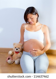 Beautiful pregnant woman sitting on floor with teddy bear