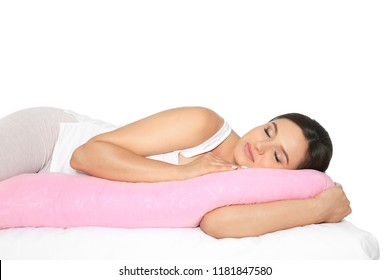 Beautiful pregnant woman sleeping with maternity pillow on bed against white background