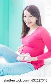 beautiful pregnant woman smiles happily on the bed with baby shoes