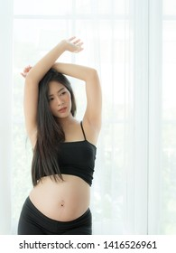 A beautiful pregnant woman standing in a room near the window and acted as a model with a beautiful posture