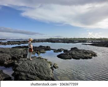 Beautiful pregnant woman in sun dress standing on rugged black rock coast