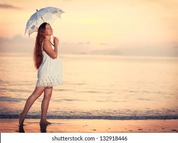 Beautiful pregnant woman at sunrise near the sea