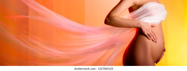 Beautiful pregnant woman touching belly flying fabric over yellow orange color panoramic background. Love and care, childbirth awaiting and new life concept, copyspace for your text