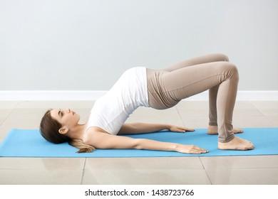 Beautiful pregnant woman training near grey wall
