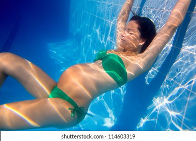 Beautiful pregnant woman underwater blue pool relaxed