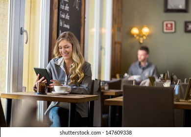 Beautiful pregnant woman using digital tablet at table in cafe