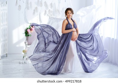 beautiful pregnant woman in violet dress luxury at the tender interior,Charming pregnant woman in flying elegant dress,Fashion pregnancy
