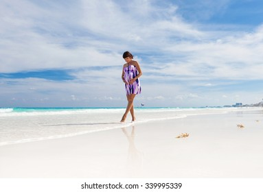 Beautiful pregnant woman walking on perfect white beach