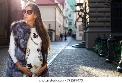Beautiful pregnant woman walking. Pregnancy, maternity, preparation and expectation concept.