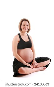 Beautiful pregnant woman wearing yoga clothes, sitting on the floor.