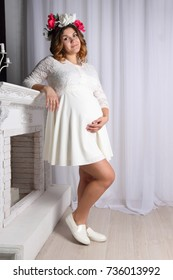 beautiful pregnant woman in white dress and wreath in her hair is standing near fireplace, hand lies on belly