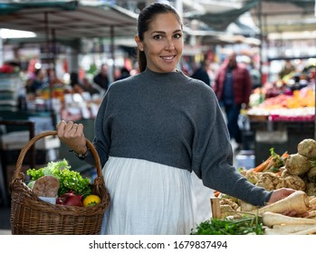 Beautiful pregnant women is buying groceries on the market