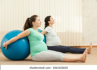 Beautiful pregnant women doing yoga with a ball