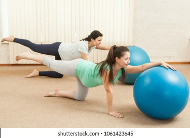 Beautiful pregnant women doing yoga on the balls
