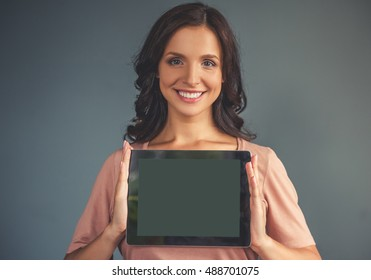 Beautiful pregnant young woman in casual clothes is holding a digital tablet, looking at camera and smiling, on a gray background