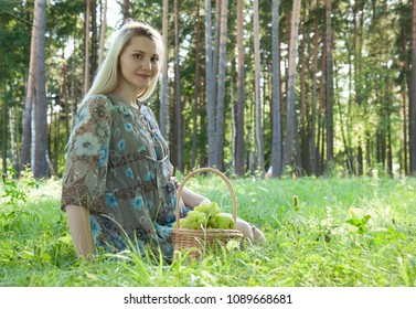 Beautiful pregnant young woman relaxing in a sunny summer park