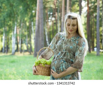 Beautiful pregnant young woman walking in a summer park with a basket full of fresh fruits