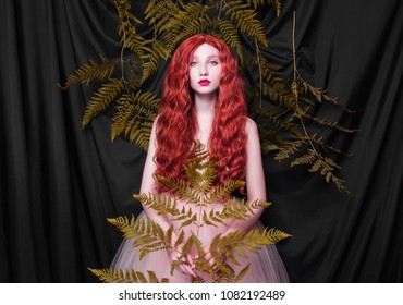 Beautiful pre-raphaelite girl with curly red hair with a flying tulle dress on black background