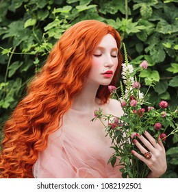 Beautiful pre-raphaelite girl with curly red hair with a flying tulle dress on the background of a fern