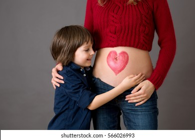 Beautiful preschool child, hugging his pregnant mom, happily expecting to be big brother. Red heart drawn on mothers belly, child kissing her little belly