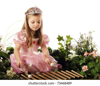 A beautiful preschool princess playing xylophone pipes while surrounded by flowers and foliage.